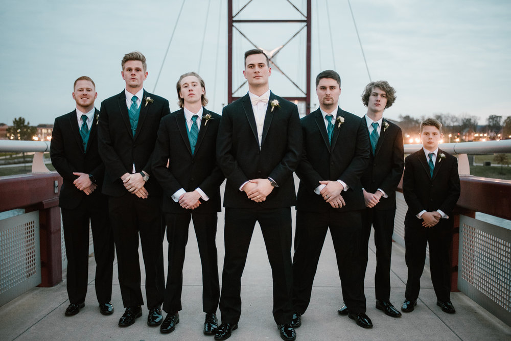groomsmen pose for picture at mishawaka river walk