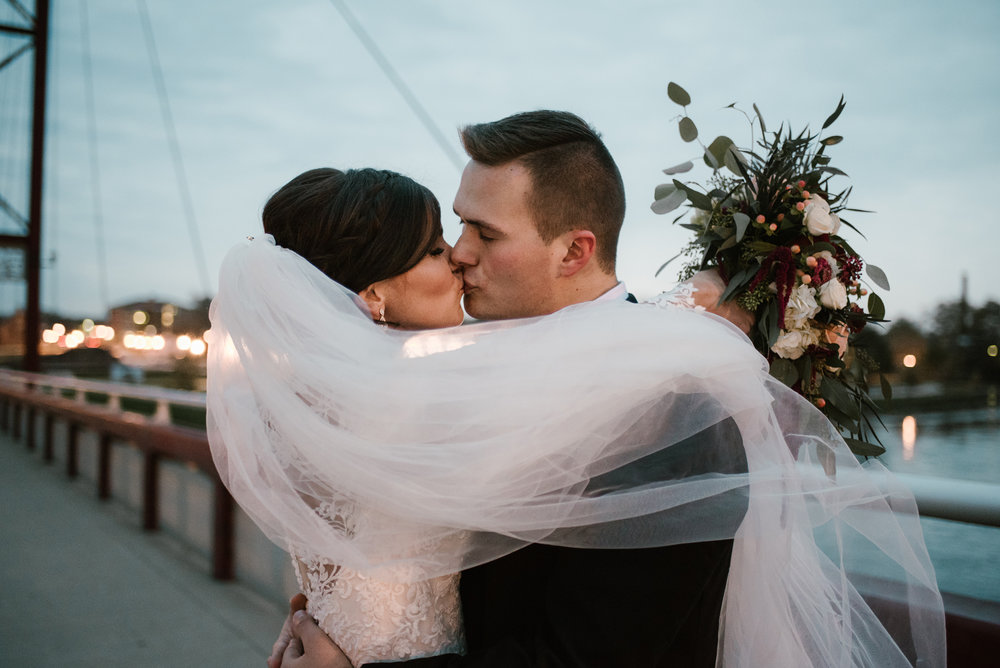 bride and groom kiss at mishawaka river walk