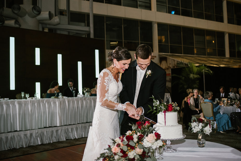 bride and groom smile while cutting cake