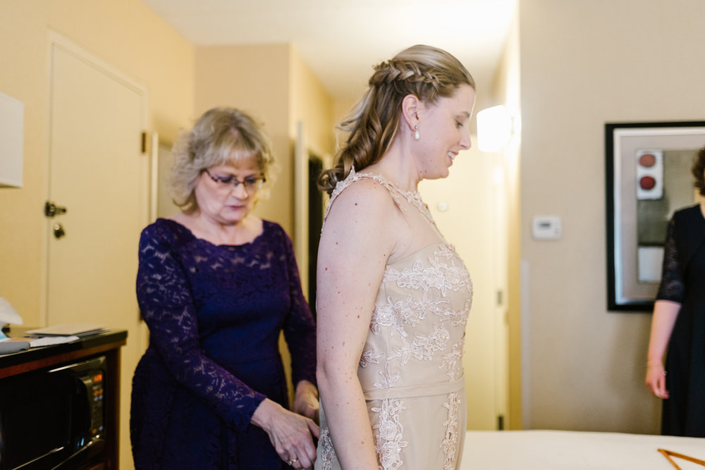 bride getting dress on, mom of bride helping