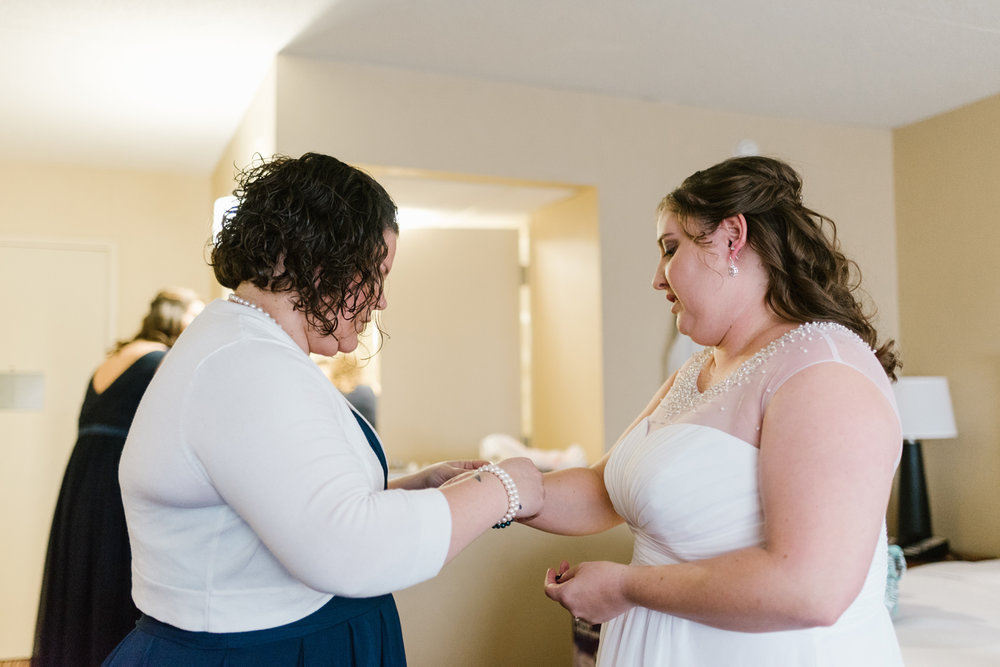 bridesmaid helping bride with getting bracelet on