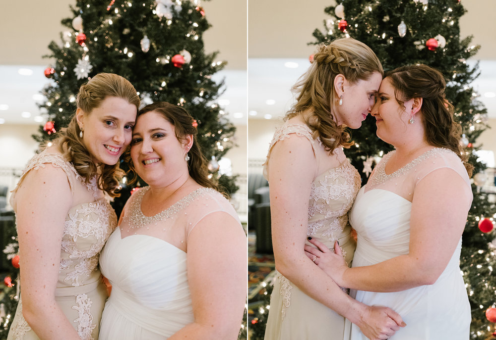 brides posing in front of christmas tree