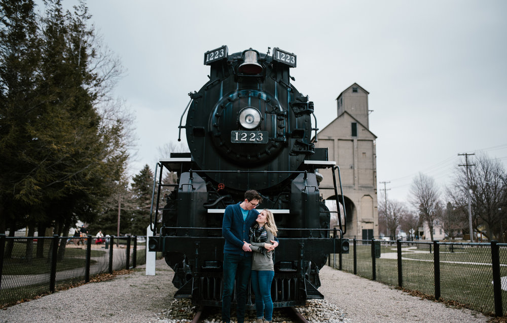 Couple posing in front of train