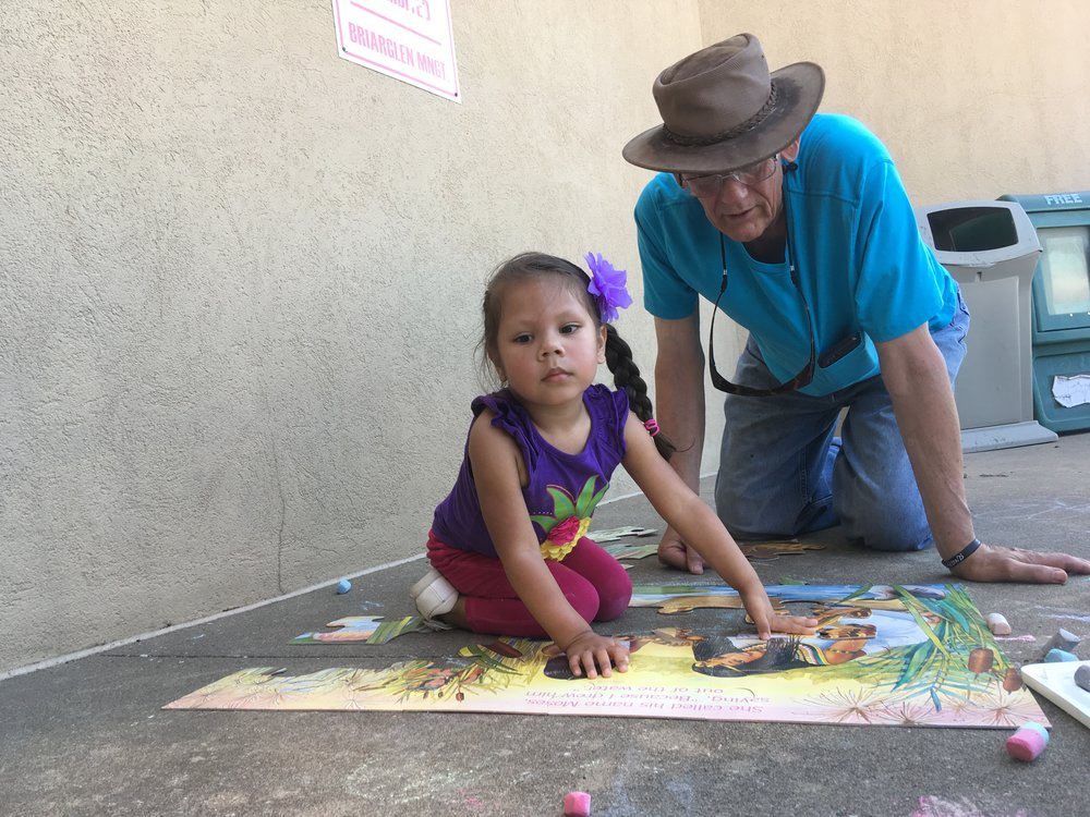 Sophia Romero working a sidewalk puzzle with The Journey Shepherd John.