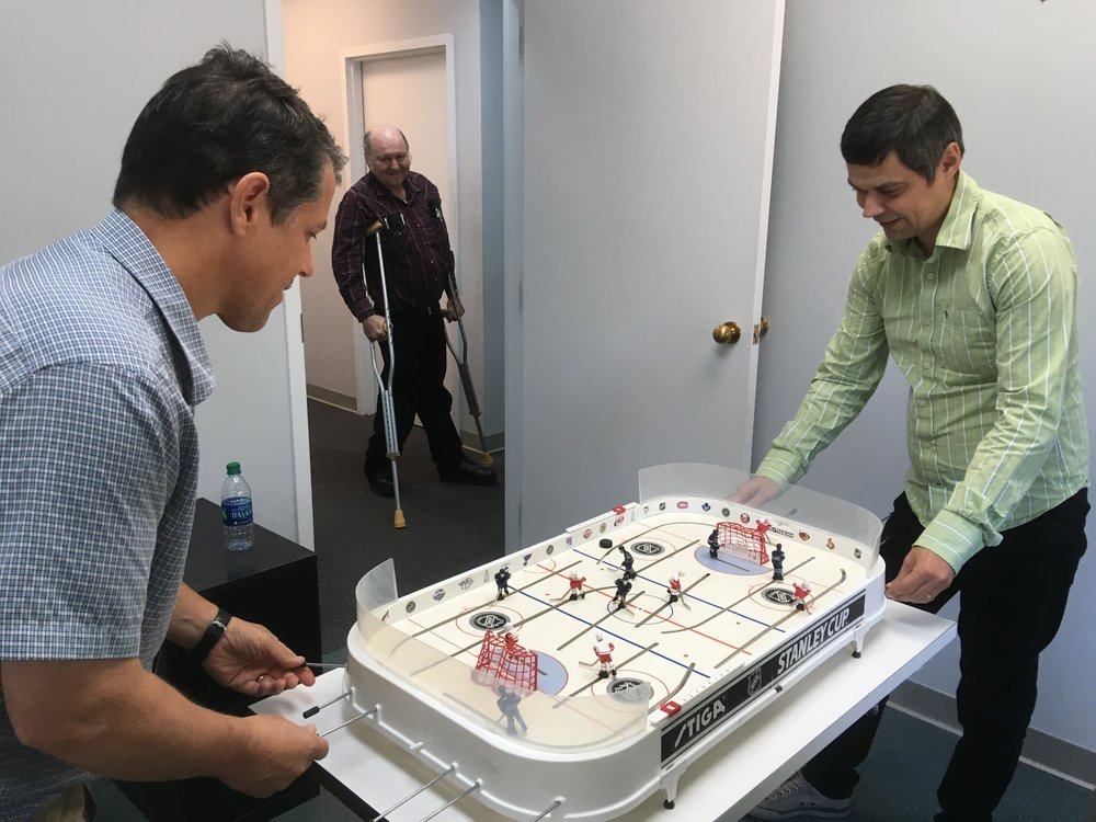 Igor Ponomarev and Greg Taylor play hockey as Real Peloquin looks on