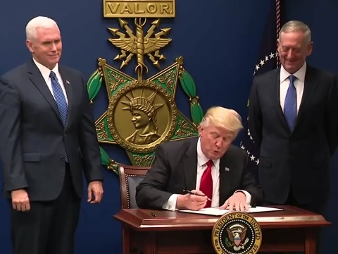 "President Trump signs Executive Order 13769, ""Protecting the Nation from Foreign Terrorist Entry into the United States"" as Vice President Mike Pence and Secretary of Defense James Mattis look on."