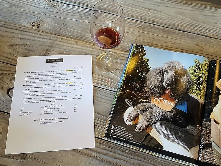 Treasure Island Wines' tasting menu and a page from a book on vineyard dogs.