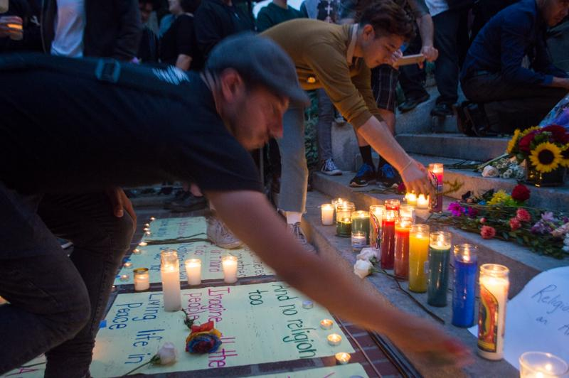 People place candles and flowers at a memorial during a candlelight vigil and rally, hosted by the Los Angeles LGBT center, at Los Angeles City Hall on Monday, June 13, 2016. (Josue Martinez)