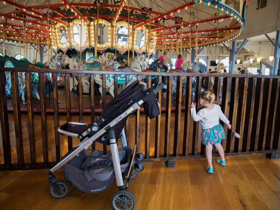 A girl looks through wooden bars towards the carousel at Santa Monica Pier in Santa Monica, Calif. on Friday, Sept 16, 2016. (Andrew Aono)
