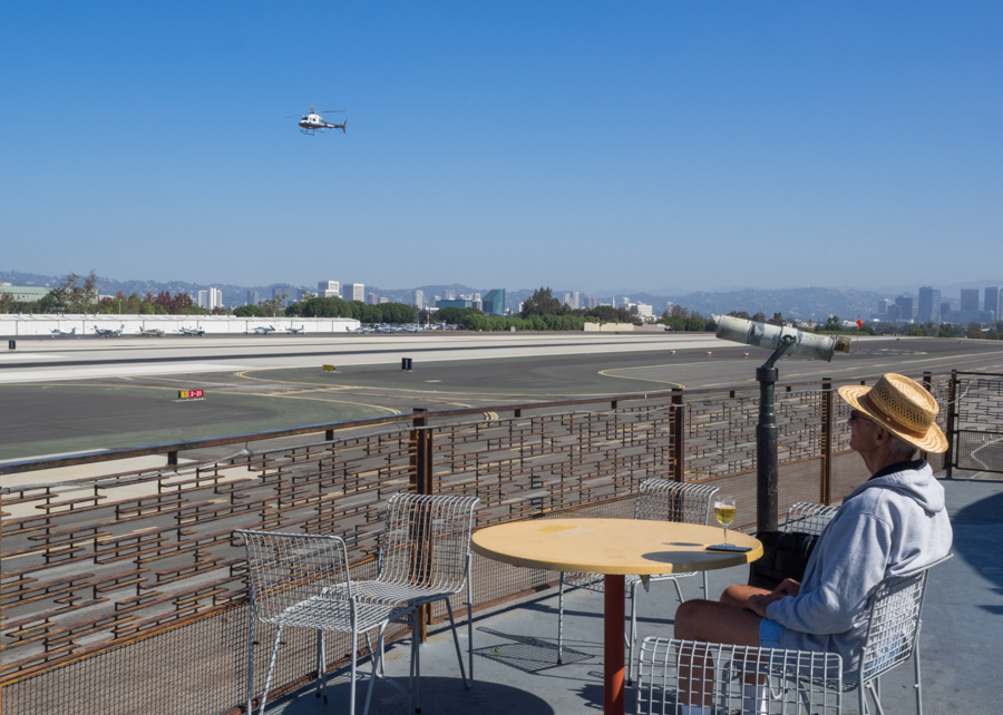"A man enjoys wine while watching a helicopter land at Santa Monica Airport in Santa Monica, Calif. on Friday, Sept 16, 2016.  Santa Monica Airport has been used to film various movies, including ""The Big Lebowski"" and ""Point Break.""  (Andrew Aono)"