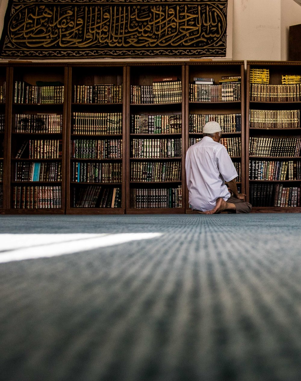 A man sits and prays in the library of the Fahad Mosque in Culver City, Calif.