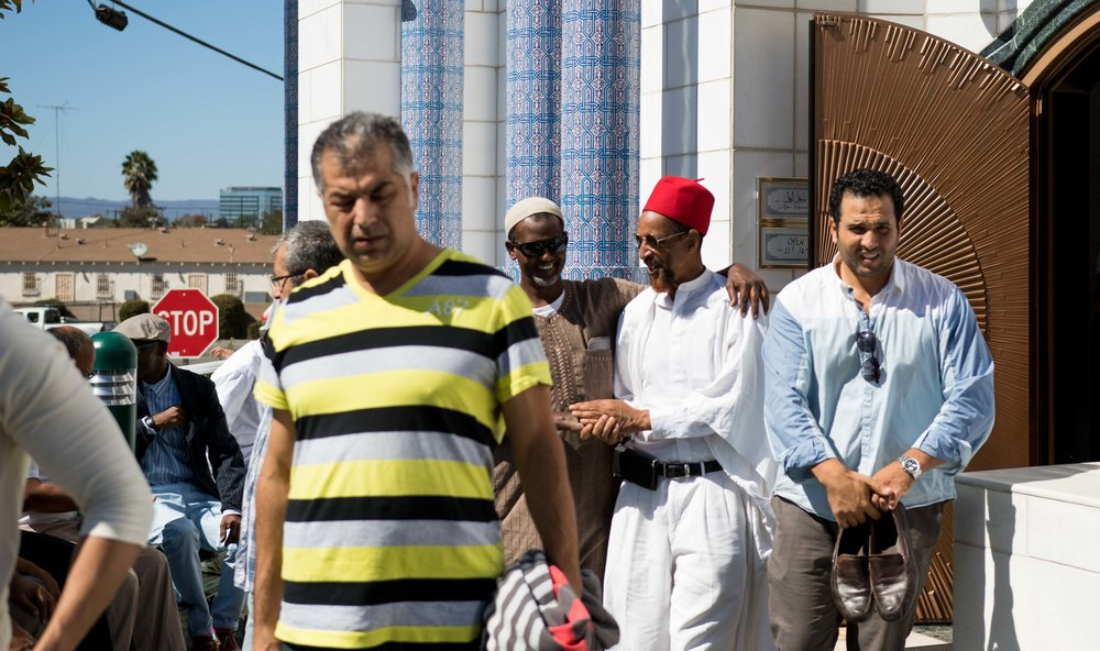 Two men shake hands after leaving their mid-day prayer at the Fahad Mosque.