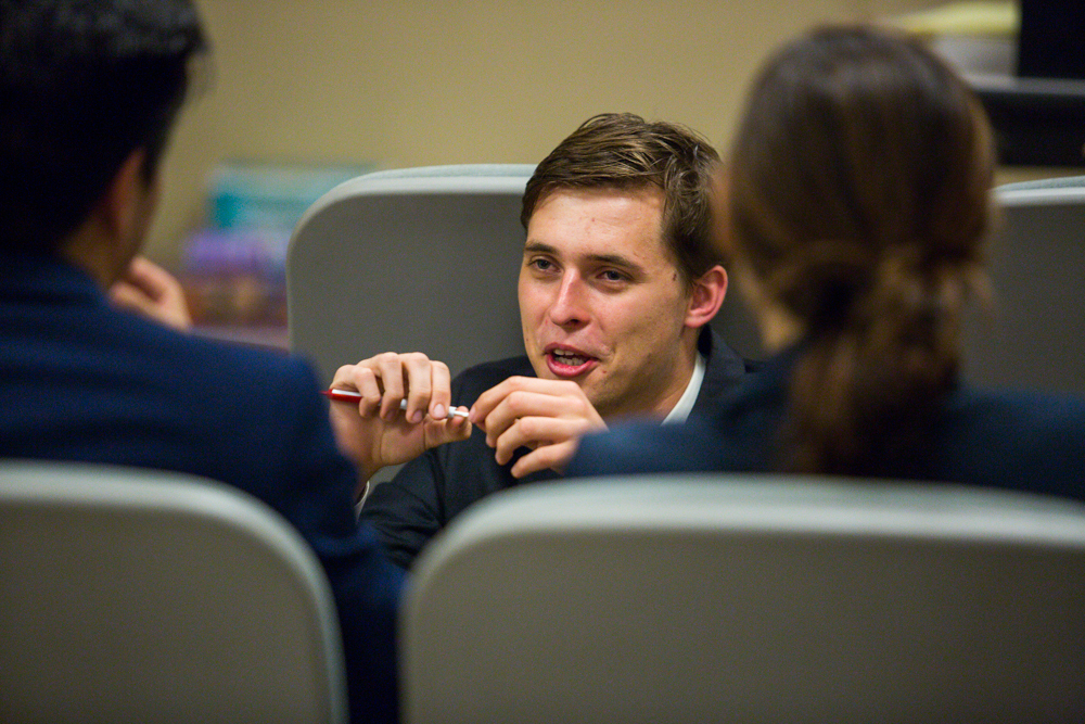 Filipp krasovsky, an economics major at UCLA and an SMC alum, sits crouched down interacting with other students as they await the final results of the debate competition held at Santa Monica College in Santa Monica, Calif. on October 28, 2016. (Jose Lopez)