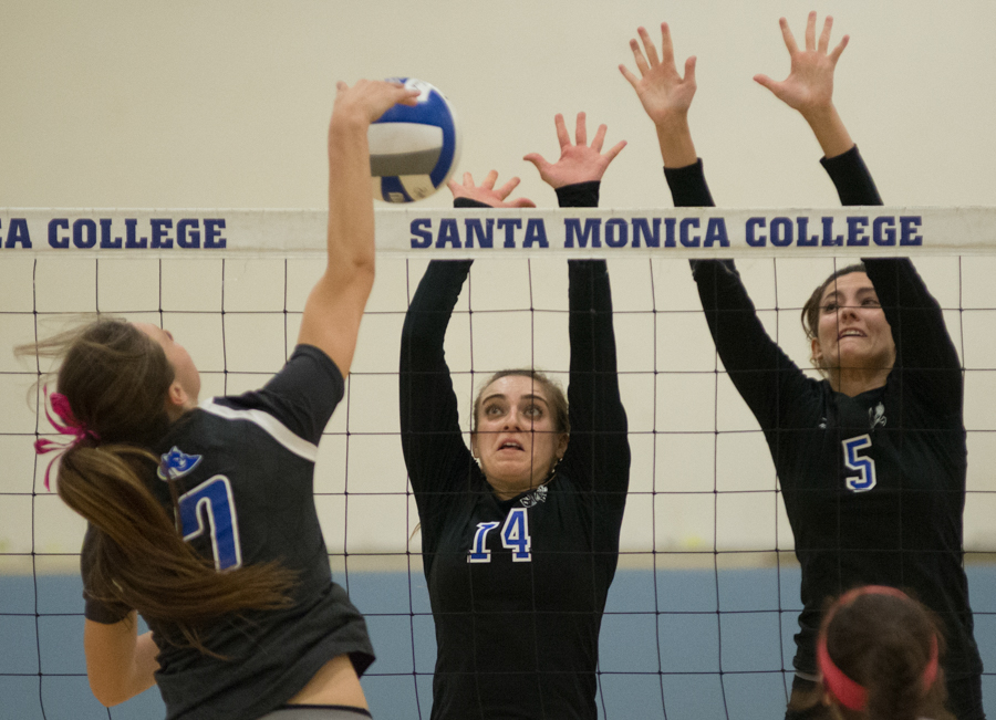 Santa Monica Corsair's Morgan Tarpley (14) (center) and Rachel Monesabian (5) (right) block West Los Angeles Wildcat middle blocker, Jessica Welchance (7) (left) during a volleyball match in the Corsair Gym on October 12, 2016 in Santa Monica, Calif. (Rosangelica Vizcarra)
