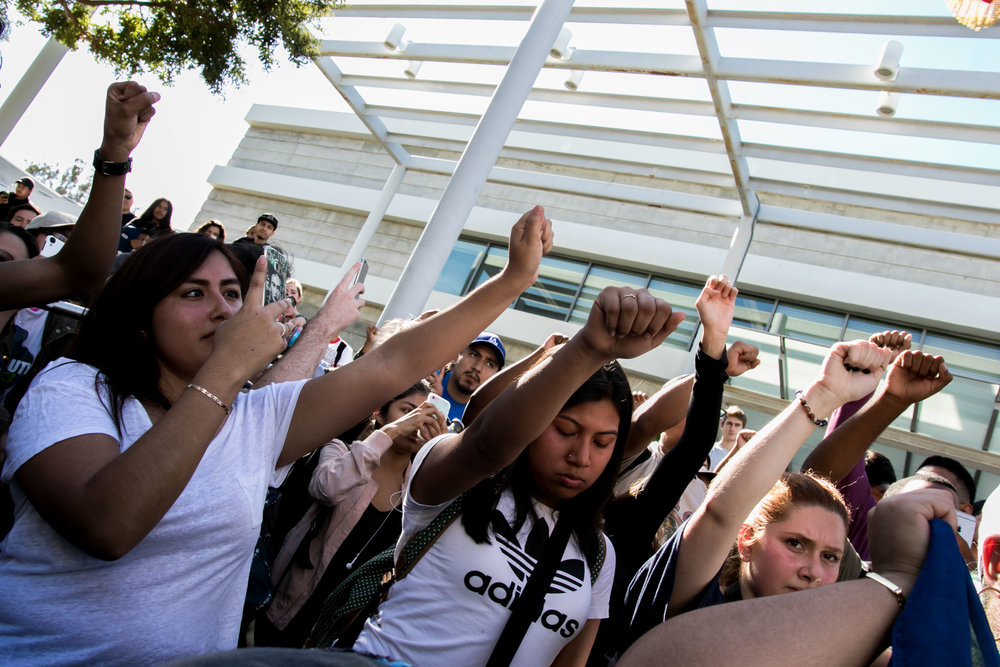 Associated Students Director of Publicity, Clara Prado, (right) raises her hand in support of SMC students protesting the nomination of Donald Trump on Wednesday.