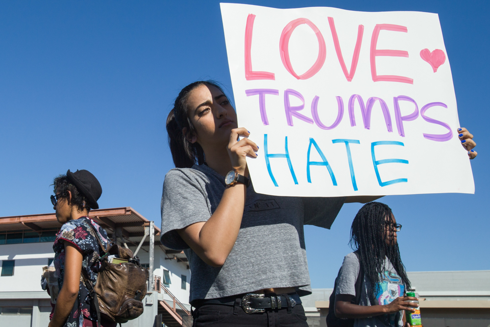 "Santa Monica College student psychology major, Kyana Shajari, 17 (center) holds the sign 'LOVE TRUMP HATE' during an on-campus Election Grief Counseling Awareness meeting designed to help students learn about and comprehend the election and its outcome at Santa Monica College in Santa Monica, Calf. on November 10, 2016. ""I feel very betrayed, devastated. The progress women have made over the years is gonna be undone. We just have to stand together and strand against opposition,' Shajari shares. (Photo by: Yulia Morris)"