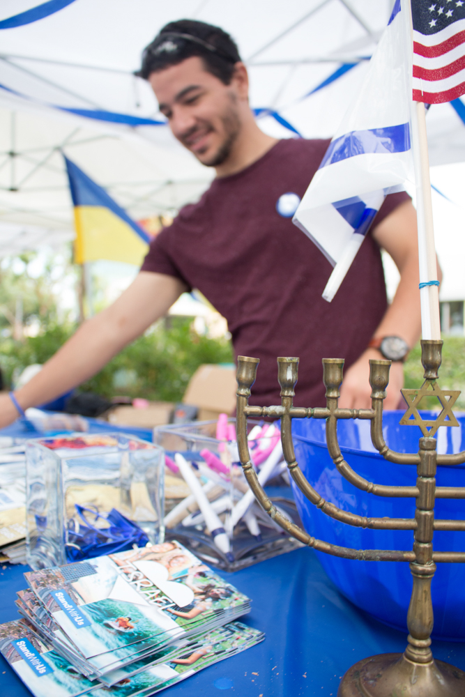 Santa Monica College student, Natan Dahan, helps promote the Students Support Israel organization (SSI) during the International Day celebration on the Santa Monica College Quad on Tuesday Nov. 15, 2016. (Marisa Vasquez)
