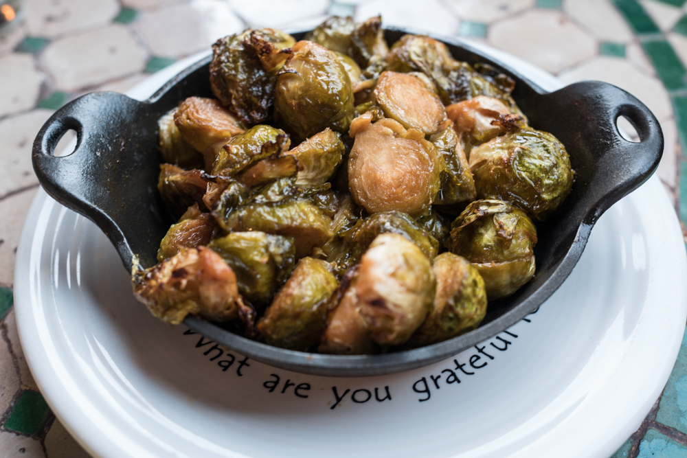 'Ecstatic', maple miso brussels sprouts, are served in an iron pan at  Cafe Gratitude in Venice Calif, on December 3, 2016. Happy hour price is $6. Regular price is $13. Photo by Yulia Morris.