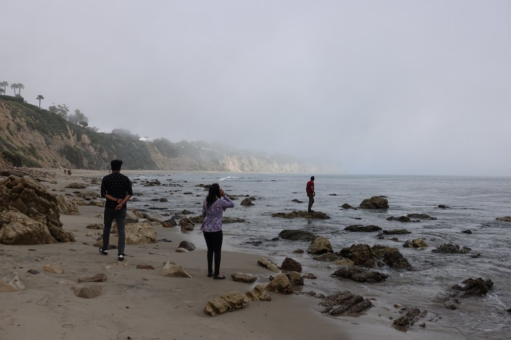Haim Abadi, 38, explores the tide pools as his family looks on.