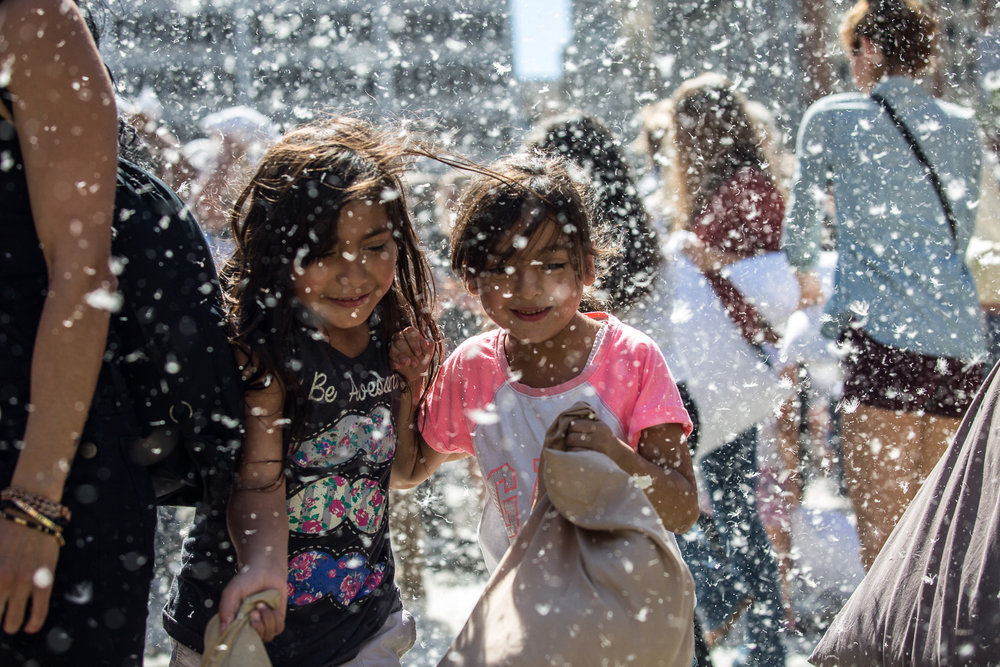 Two young pillow fight participants hurry to get out of the cross fire of feathers and pillows during the annual International Pillow Fight Day fight in Pershing Square in Downtown Los Angles on Saturday, April 1 2017. Hundreds of people traded soft blows in a giant pillow fight that dwarfed even the biggest slumber party slugfest. Children, teens, adults and seniors swung pillows at one another for over 2 hours during Saturdays event. (Corsair Photo: Matthew Martin)