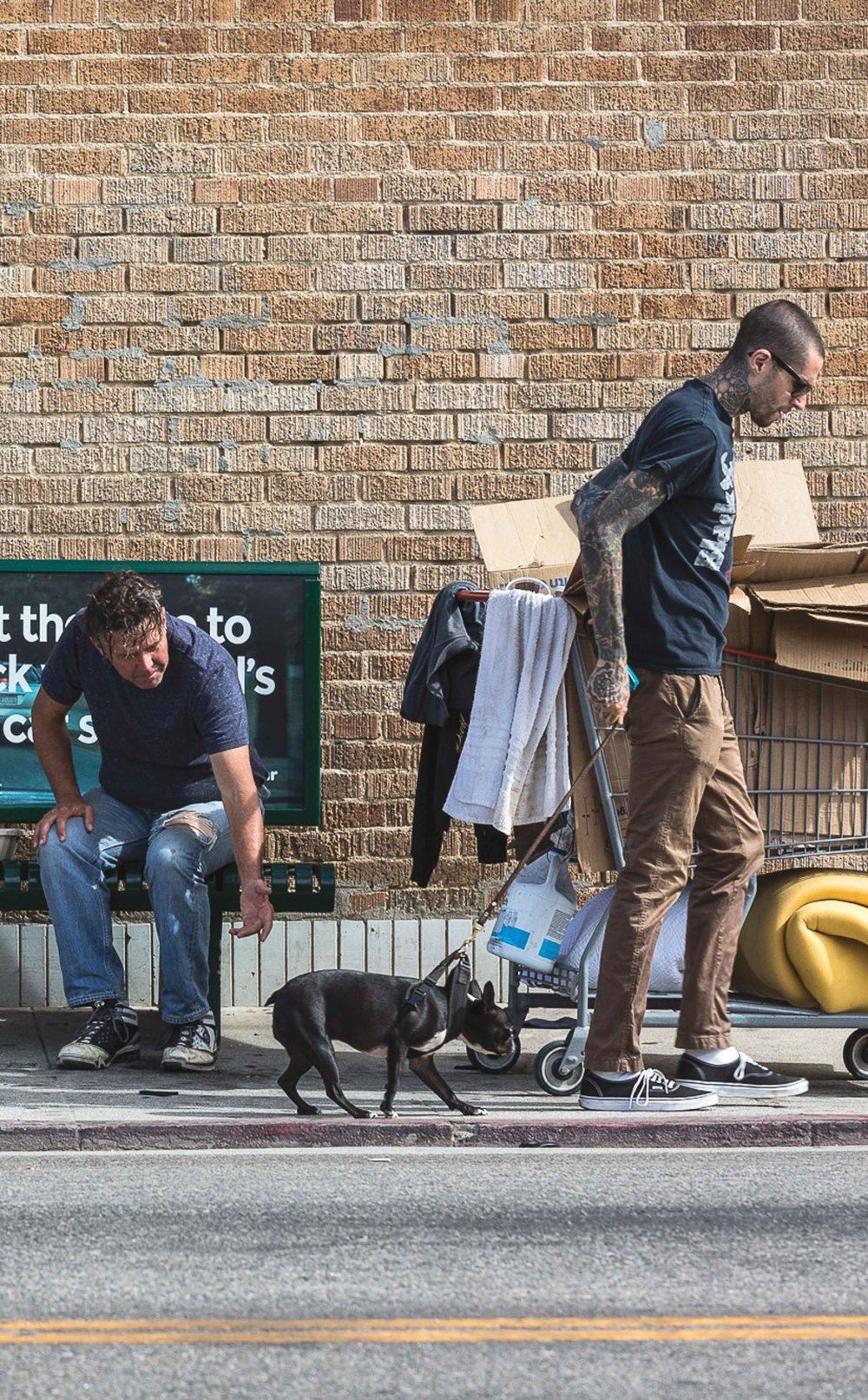 "Floyd (left), 55, a frequent roamer of Venice streets attempts to pat a local hipsters dog as it is pulled away by the owner on Westminster Ave in Venice, CA on October 16, 2016. The photograph illustrates the overlooked past and privileged present of the area and how gentrification is pushing the homeless out of the ""hippest street in the United States."" (Photo by Matthew Martin)"