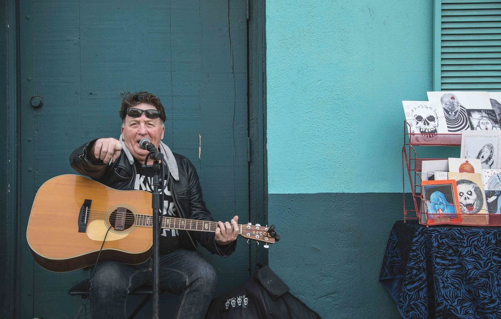 "David Carroll, (56,) a musician and post card artist busks outside the now shuttered Roosterfish bar on Abbot Kinney Blvd in Venice, CA on November 6 2016. Carroll adores Abbot Kinney and has lived in the area for over 20 years. He comes each weekend to sing because this area, and in particular this street, make him feel nostalgic and joyful and when asked for his opinion on Abbot Kinney's growing gentrification he commented, ""It's two-sided because before Abbot Kinney started getting gentrified 20 years ago, it was a much more dangerous place, now the only danger are those damn hipsters."" (Photo by Matthew Martin)"