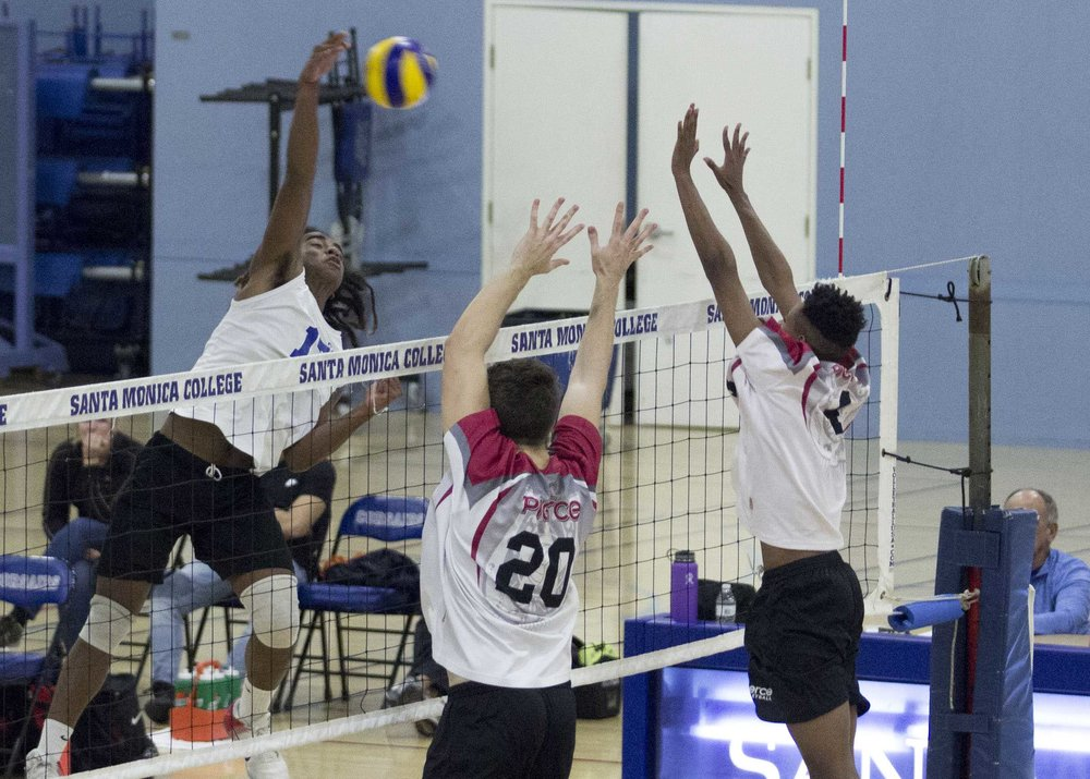 Santa Monica College Corsair freshman outside hitter Dane Pieper (17, left) attempts to spike the ball through Pierce College Brahmas freshmen defenders Brenton Scott (20, middle) and Mario Patrick (4, right) in the SMC Gymnasium at Santa Monica College in Santa Monica, CA. on wednesday, March 1, 2017. On the way to the Corsairs clean sweep of the Brahmas (3-0). (Corsair Photo: Zane Meyer-Thornton)