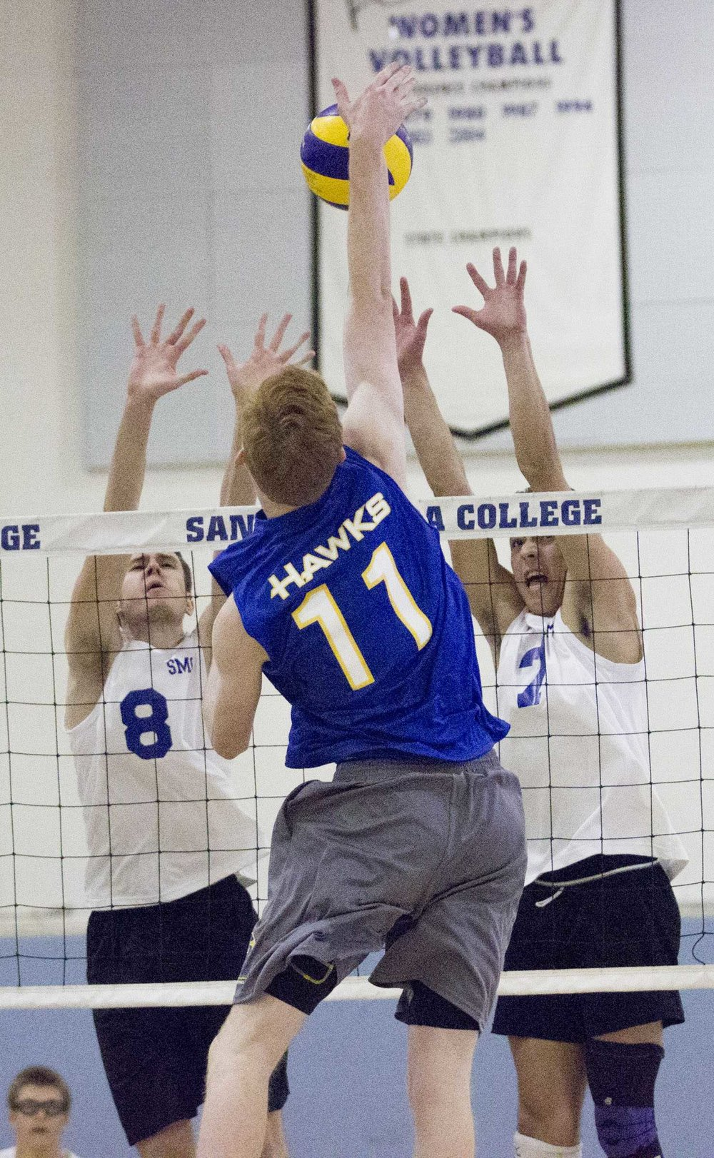 Santiago Canyon College Hawks freshman opposite hitter Andrew Desrochers (11, center) spikes the ball between Santa Monica College Corsairs freshman middle blocker Nick Kotetsky (8, left) and Santa Monica College Corsairs freshman left blocker AJ Peyrot (22, right) at the Santa Monica College gymnasium, in Santa Monica California on March 10, 2017. (Corsair Photo: Zane Meyer-Thornton)