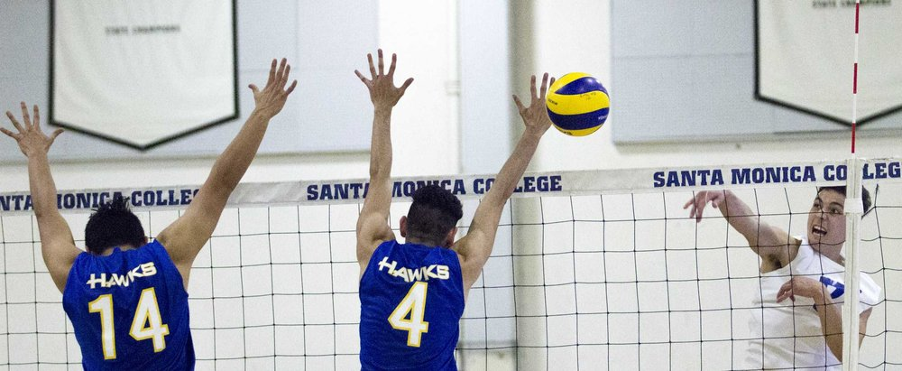 Santiago Canyon College Hawks freshman middle blocker Gustavo Marquez (14, left) and Santiago Canyon College Hawks freshman setter Christopher Solares (4, middle) attempt to block the attack of Santa Monica College Corsairs freshman outside hitter Max Ball (7, right) at the Santa Monica College gymnasium, in Santa Monica California on March 10, 2017. (Corsair Photo: Zane Meyer-Thornton)