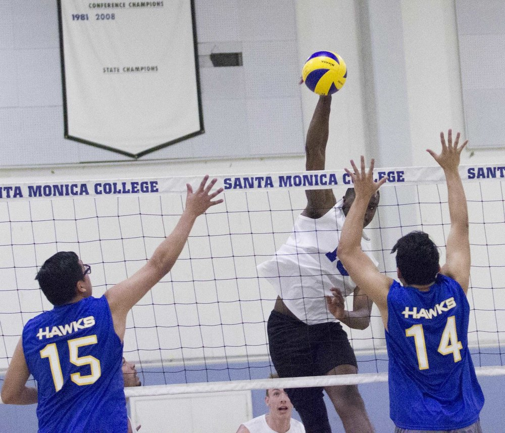 Santa Monica College Corsairs freshman middle hitter Vecas Lewin (15, center) spikes the ball as Santiago Canyon College Hawks freshman opposite hitter Geovani Ponce (15, left) and Santiago Canyon College Hawks freshman middle blocker Gustavo Marquez (14, right) attempt to deflect it at the Santa Monica College gymnasium, in Santa Monica California on March 10, 2017. (Corsair Photo: Zane Meyer-Thornton)