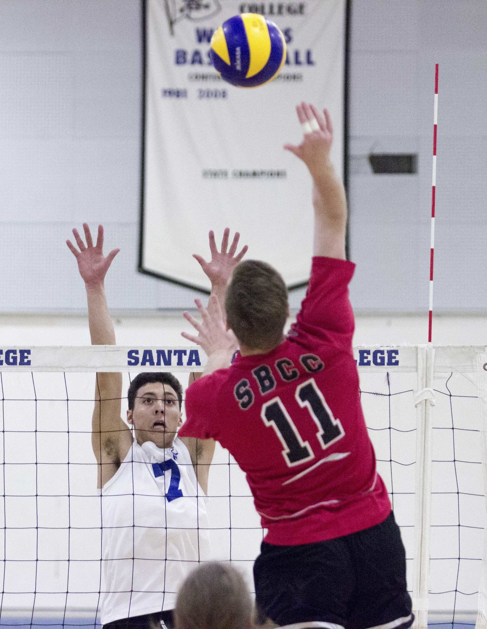Santa Barbara City College Vaqueros sophomore right side hitter Sean Reynaert (11, right) spikes the ball down as Santa Monica College Corsairs freshman outside hitter Max Ball (7, left) attempts a block on the way to a 3-0 victory for the Corsairs on March 15, 2017 in the Santa Monica College Gymnasium at Santa Monica College in Santa Monica California (Photo By: Zane Meyer)