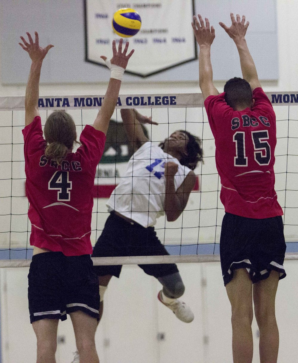 Santa Monica College Corsairs freshman outside hitter Dane Pieper (17, center) attempts to split the defense of Santa Barbara City College Vaqueros freshmen middle blockers Stephen Trevitt (4, left) and Jarrett Futch (15, right) as part of the Corsairs 3-0 victory on March 15, 2017 in the Santa Monica College Gymnasium at Santa Monica College in Santa Monica California (Photo By: Zane Meyer)
