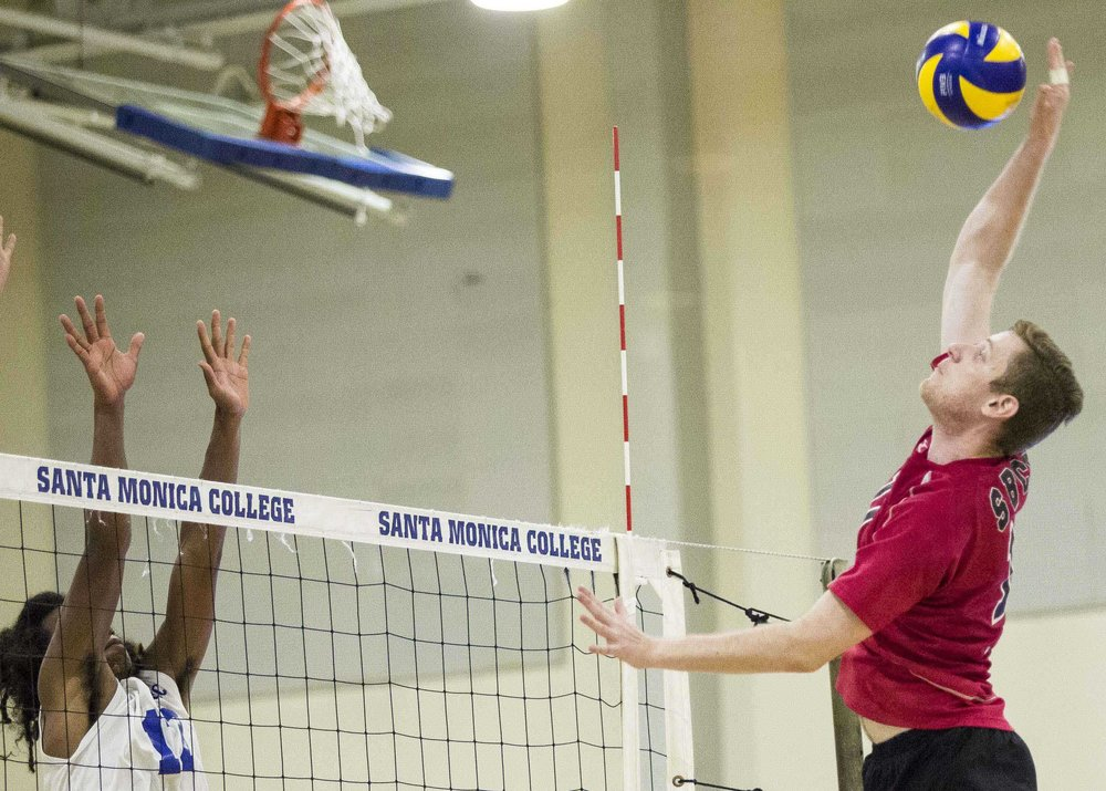 Santa Monica College Corsair freshman outside hitter Dane Pieper (17, left) prepares for the powerful strike coming from the Santa Barbara Vaqueros sophomore right-side hitter Sean Reynaert (11, right) in the Santa Monica College Gymnasium at Santa Monica College in Santa Monica California on March 15, 2017. The Santa Monica Corsairs were able to sweep the Santa Barbara Vaqueros 3-0 by the end of the game. (Corsair Photo: Matthew Martin)