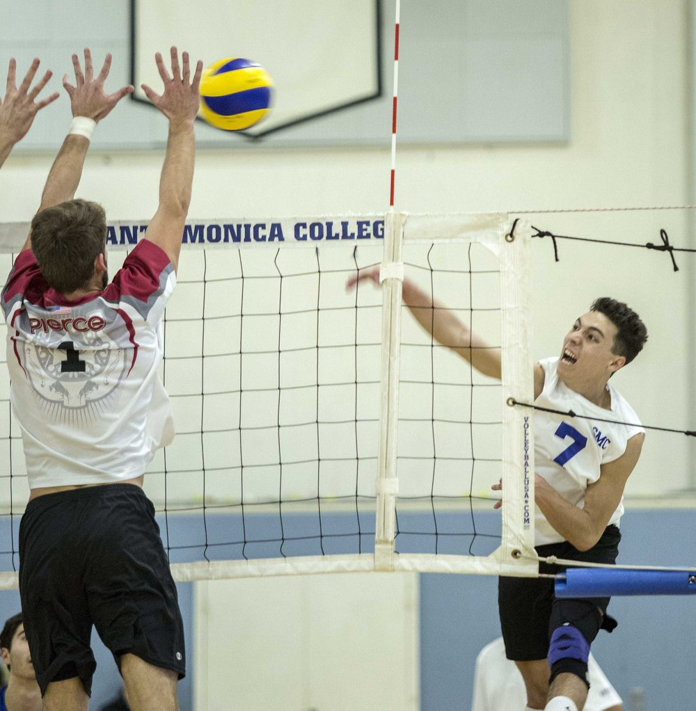 Santa Monica College Corsair freshman outside hitter Max Bell  (7, right) spikes the ball as the Pierce College Brahmas freshman opposite hitter Brandon Oswald (1, left) attempts to block the ball in the SMC gymnasium at Santa Monica College in Santa Monica Calif., on Wednesday, March 1 2017. The Corsairs were able to sweep the Brahmas 3-0 by the end of the game. (Corsair Photo: Matthew Martin)