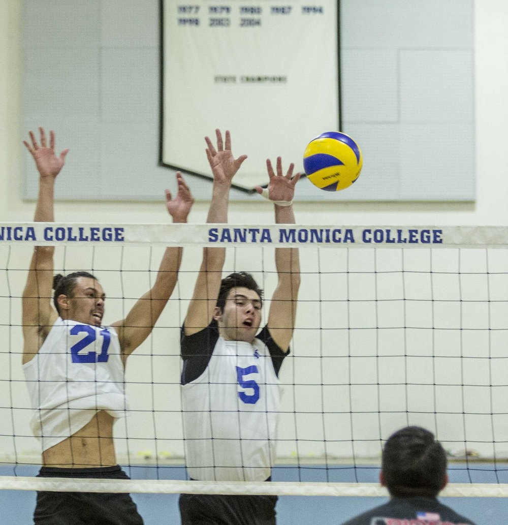 Santa Monica Corsairs freshmen setter Hunter Douglas (21, left) and freshmen middle blocker Andrew Dalmada (5, right) successfully block the ball in the Santa Monica College gymnasium in Santa Monica Calif., on Wednesday March 1 2017. The Corsairs were able to sweep the Brahmas 3-0 for the win by the end of the game. (Corsair Photo: Matthew Martin)