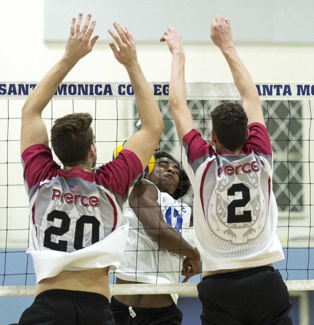 Santa Monica College Corsair freshman outside hitter Dane Pieper (17, center) fails to spike the ball when it is blocked by the Pierce College Brahmas defenders freshman middle blocker Brenton Scott (20, left) and by freshman opposite hitter Trenton Sellers (2, right) in the Santa Monica College gymnasium in Santa Monica Calif., on Wednesday March 1 2017. The Corsairs were able to sweep the Brahmas 3-0 for the win by the end of the game. (Corsair Photo: Matthew Martin)