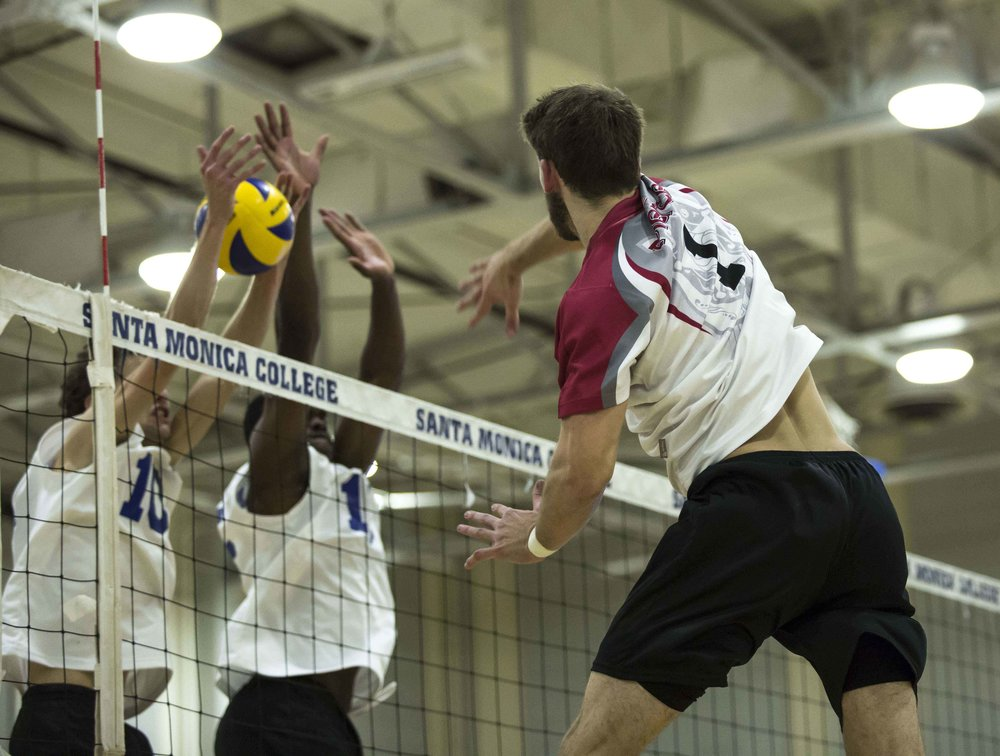 The Santa Monica Corsair defenders attempt to block the incoming spike by Pierce College Brahmas freshman opposite hitter Brandon Oswald (1, right) in the Santa Monica College gymnasium in Santa Monica Calif., on Wednesday March 1 2017. The Corsairs were able to sweep the Brahmas 3-0 by the end of the game. (Corsair Photo: Matthew Martin)