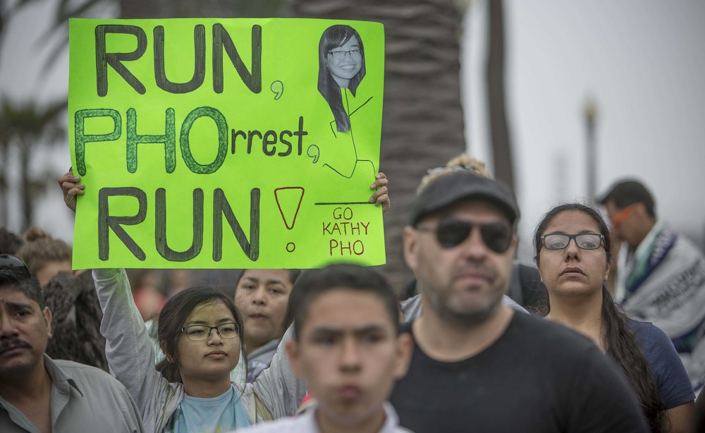 March 19, 2017. Katrina Pho holds up a sign waiting for her sister Kathy Pho to cross the finish line during the LA Marathon in Santa Monica, California. Daniel Bowyer