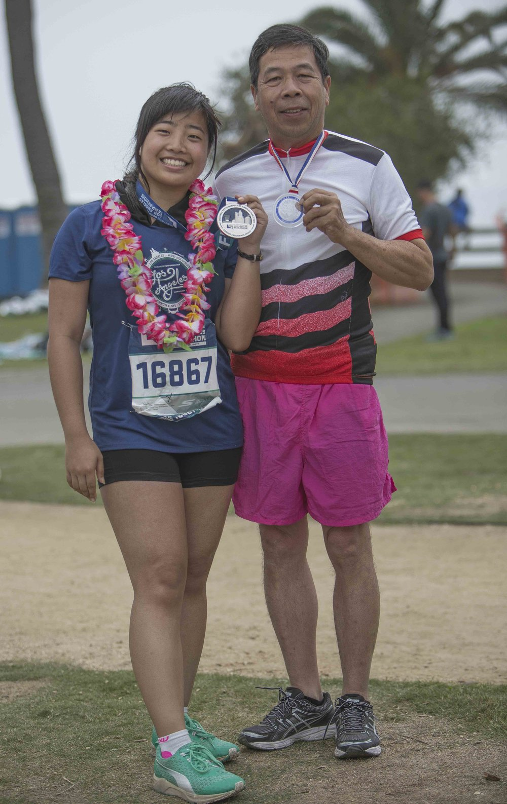 March 19, 2017. Kathy Pho (left) shows off her medal after completing The La Marathon and stands with her father Que Pho (right) who ran The LA Marathon in 1994 show off his medal. Kathy Pho finished the marathon in five hours fourty nine minutes fifty four seconds. Santa Monica, California. Photo by Daniel Bowyer.