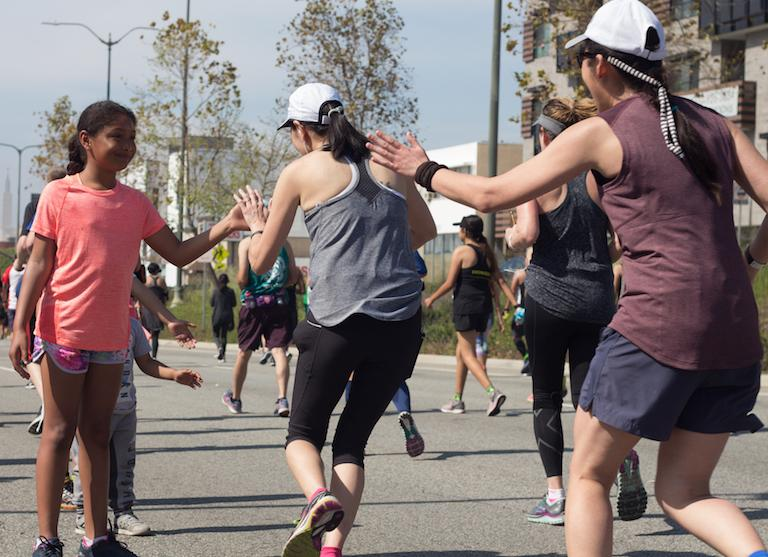 Kids showing their support to L.A. Marathon runners by giving out high-fives at 17-mile mark in Beverly Hills, CA., on March 19, 2017. Photo by Ethan Chuang