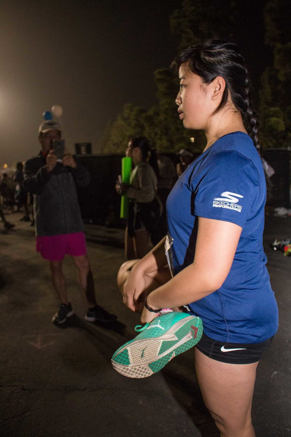 Santa Monica College Acssociated Students Activities Director, Kathy Pho (right) stretches before her 26.2 mile treck as preporation for the 2017 Skechers Performance LA Marathon on Sunday March 19, 2017 at the Dodger Stadium in Los Angeles, CA. Pho's Father, Que Pho (left), snaps a picture of her as she focuses on the 26.2 mile run she has been training for. Photo by Marisa Vasquez.