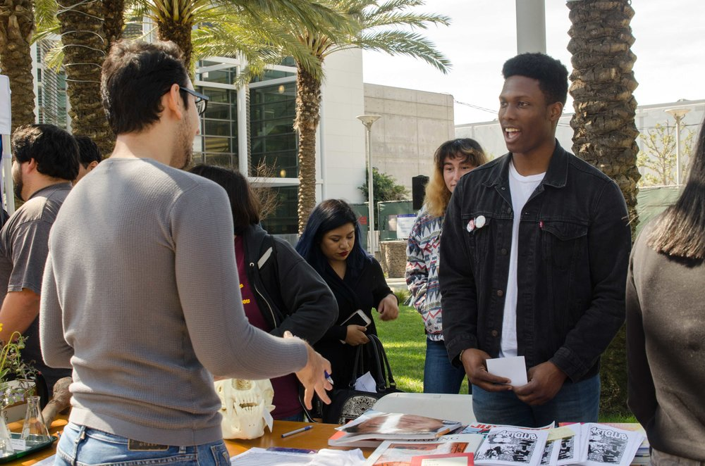 Gozie Ojini(Right) recruiting Santa Monica College Students for the Art Club at Club Awareness Day at Santa Monica College in Santa Monica, California on March 14, 2017 (Photo By: Diana Parra Garcia)