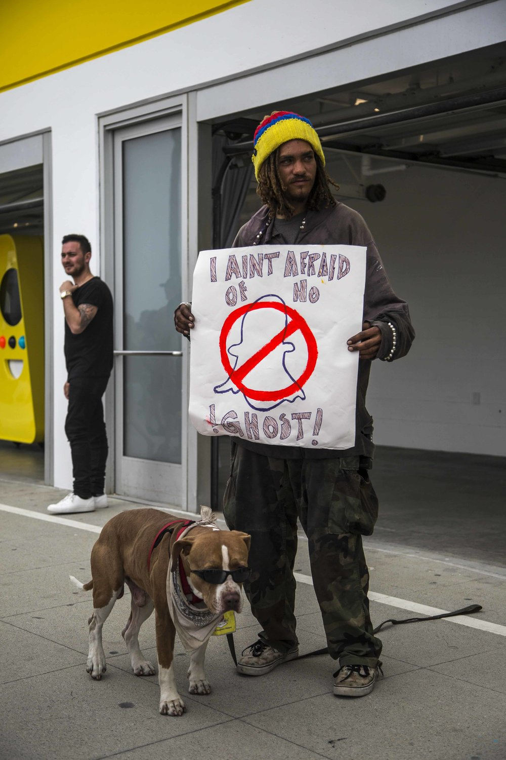 "Local Venice artist and activist Josiah Renn protests Snapchats newly opened storefront named Spectacles holding a sign which reads, ""I aint afraid of no ghost"" at 701 Ocean Front Walk, Venice, Calif., on Saturday March 11 2017.  Renn argues that Snapchats presence is the culprit for rising rents and the takeover of local cafes and other properties by Snap. ""This is one of the few remaining artist communities left and I will fight to save it from this hostile takeover."" (Corsair Photo: Matthew Martin)"