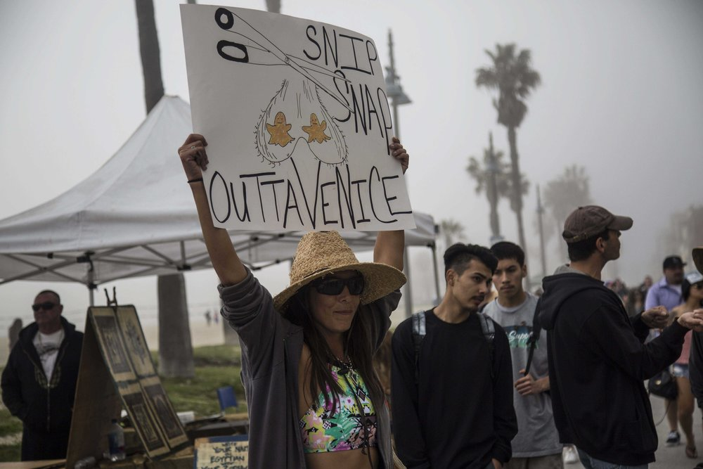 Venice local, activist and member of The Alliance for the Preservation of Venice Reina Storm protests outside of Snapchats newly opened storefront, Spectacles at 701 Ocean Front Walk, Venice, Calif., on March 11, 2017. Since arriving in 2013, Snap has bought homes, shops and an apartment building, converting them into guarded offices. Locals see the company as threatening their colorful, artsy neighborhood on the Venice boardwalk. (Corsair Photo: Matthew Martin)