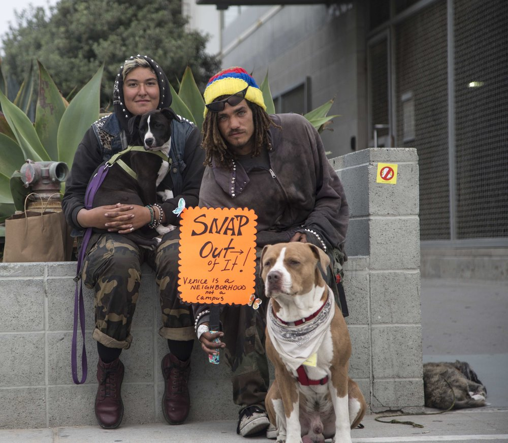 "Local Venice activist Josiah Renn (right) and his girlfriend Izzy Martin (right) protest outside Snapchats newly opened storefront named Spectacles at 701 Ocean Front Walk, Venice, Calif., on Saturday March 11 2017. The Venice locals believe ""Snapchats presence is causing an influx of a tech culture that is pushing out local artists and mom and pop shops, causing this vibrant, beautifully weird community into an unwanted Silicon Beach."" (Corsair Photo: Matthew Martin)"