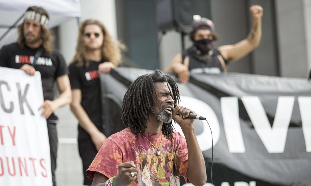 "Kor Element, a Bernie Sanders Supporter, World Peace Poet and Hip Hop Healer and NAPL activist performs a spoken word peace at the the Divest LA rally at Los Angles City Hall in Downtown Los Angles, Calif., Friday March 10 2017. Kor Element is photographed mid performance as a crowd of Divest LA demonstrators applauded him as he sings, ""Sometimes you gotta figure out what you stand for, cause if you don't stand for something, you can fall for anything"". (Photo by Matthew Martin)"