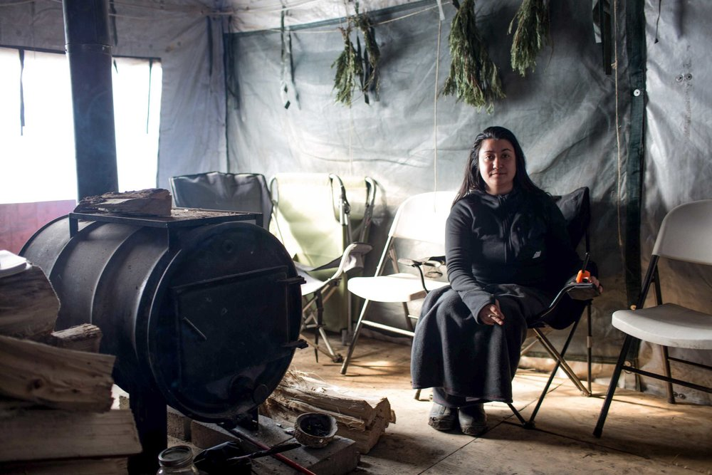 Water Protector Kei Kuromoto sits in her tent at Cheyenne River camp, established by the four bands of the Great Sioux Nation just over two weeks ago in order to provide a place for Native Americans to continue to pray and hold vigil near the site of the proposed Dakota Access Pipeline even after the fall of Oceti. Wednesday February 23rd 2017, Sacred Stone Camp, North Dakota. Photo by Ruth Lorio.