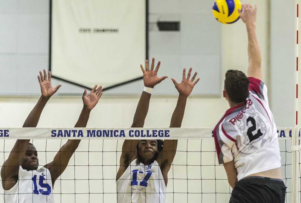 Santa Monica College Corsair freshman middle hitter Vecas Lewin (15, left) and Santa Monica Corsair freshman outside hitter Dane Pieper (17, middle) prepare to block the incoming spike from Pierce College Brahmas freshman opposite hitter Trenton Sellers (2, right) in the Santa Monica College gymnasium in Santa Monica Calif., on Friday, April 21 2017. The Corsairs would go on to win the game 3-2, which would allow the Corsairs to advance to the second round of the CCCAA playoffs. (Corsair Photo: Matthew Martin)