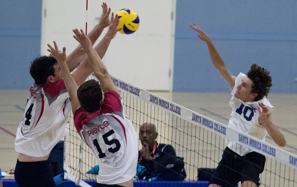 Santa Monica College sophomore right side hitter Shane Stoklos (10, right) spikes the ball into the defense of Pierce College Brahmas freshman setter Bernando Roese (14, left) and Pierce College Brahmas freshman middle blocker Max Petuhov (15, middle) as the Corsairs inch out a 3-2 victory at the Santa Monica College Gymnasium at Santa Monica College in Santa Monica California on April 21, 2017 (Photo By: Zane Meyer-Thornton)