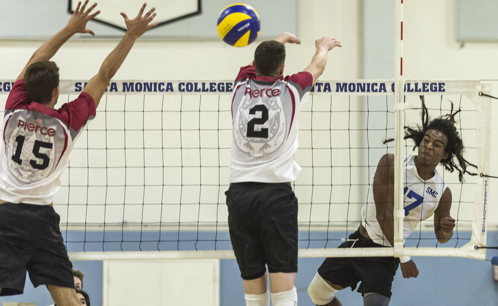 Santa Monica Corsair freshman outside hitter Dane Pieper (17, right) nails a powerful spike, which split the Pierce College defense consisting of Pierce College Brahma freshmen middle blocker Max Petuhov (15, left) and Pierce College Brahma freshmen opposite-hitter Trenton Sellers (2, middle) in the Santa Monica College gymnasium in Santa Monica Calif., on Friday, April 21 2017. The Corsairs would go on to win the game 3-2, which would allow the Corsairs to advance to the second round of the CCCAA playoffs. (Corsair Photo: Matthew Martin)